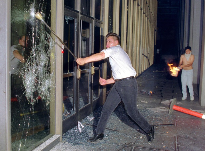 A rioter breaks a glass door of the Criminal Court